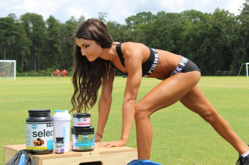 Lacey Dunn stretching in a field with PEScience products