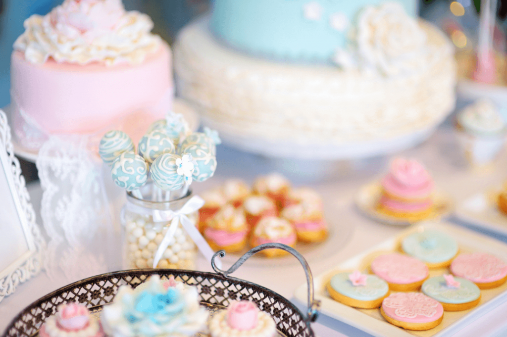 a spread of cakes, cookies, and desserts in pastel colors