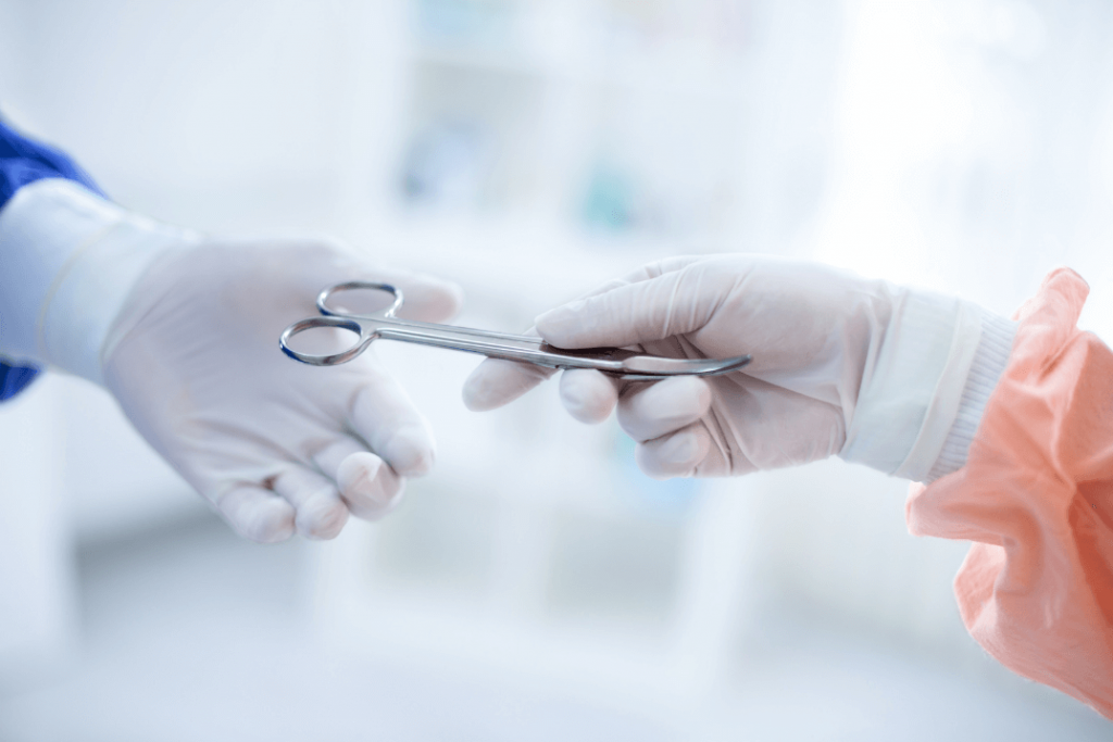 gloved doctor handing scissors to other gloved doctor