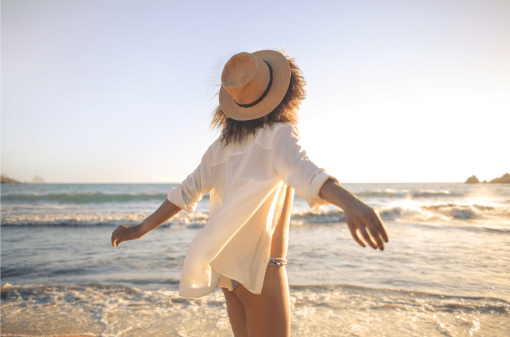 carefree woman holding out arms wide open on the beach