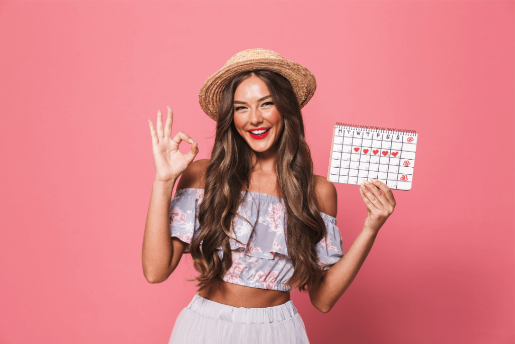 smiling woman holding up a calendar that has her period dates marked