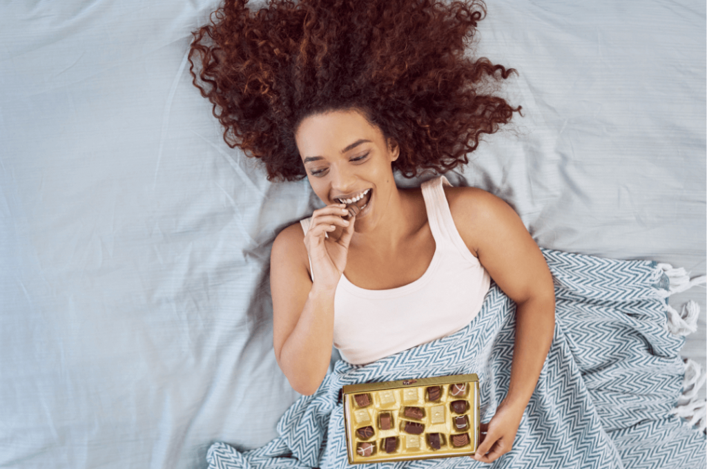 woman laying in bed eating chocolate and smiling underneath a blue blanket
