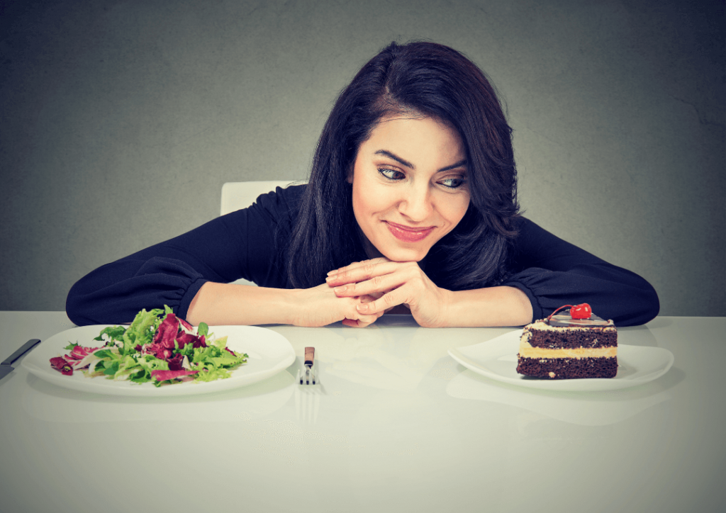 woman with two plates in front of her, staring at the plate with chocolate cake