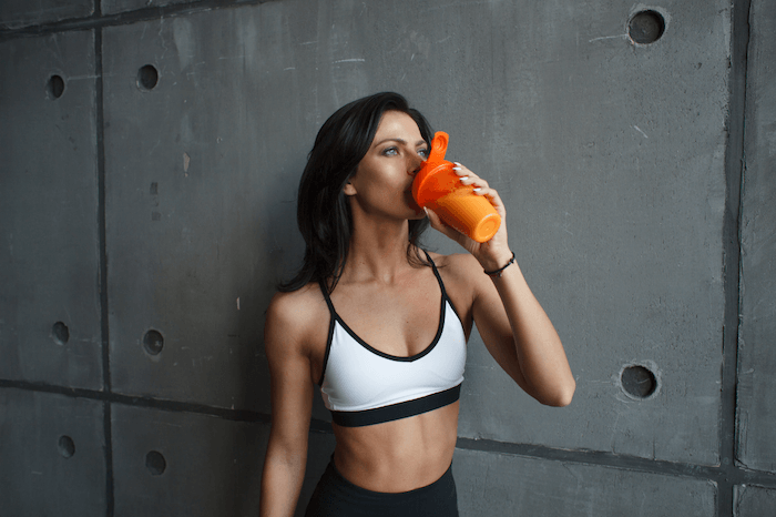 fit woman wearing white sports bra drinking protein shake from orange shaker bottle on dark background