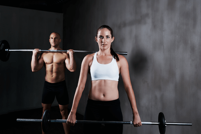 man and woman lifting weights in black shorts and white sports bra with dark background