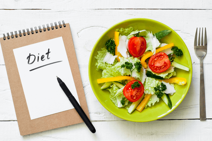 salad in a green bowl with fork and diet journal with pen on white wood table