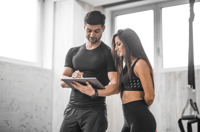 woman in black workout clothes with her trainer going over her training program with light background