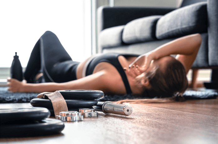 woman wearing black workout clothes laying on the ground with water bottle and weights after overtraining