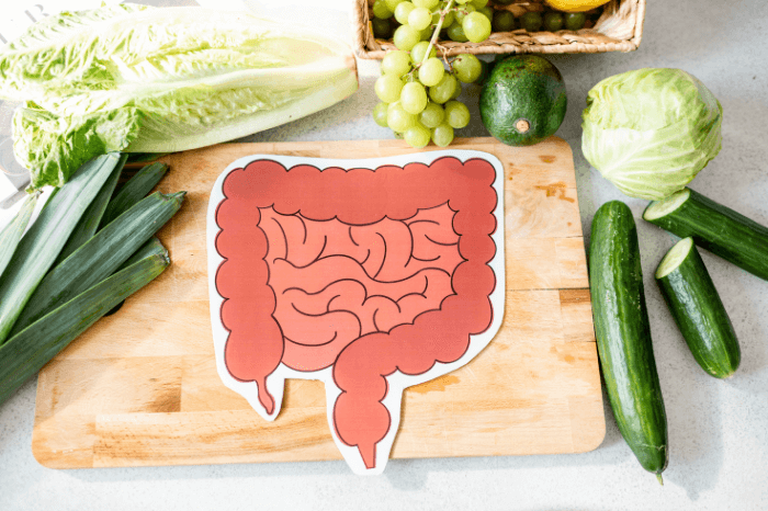 cartoon colon on wooden cutting board surrounded by green fruits and vegetables on white background