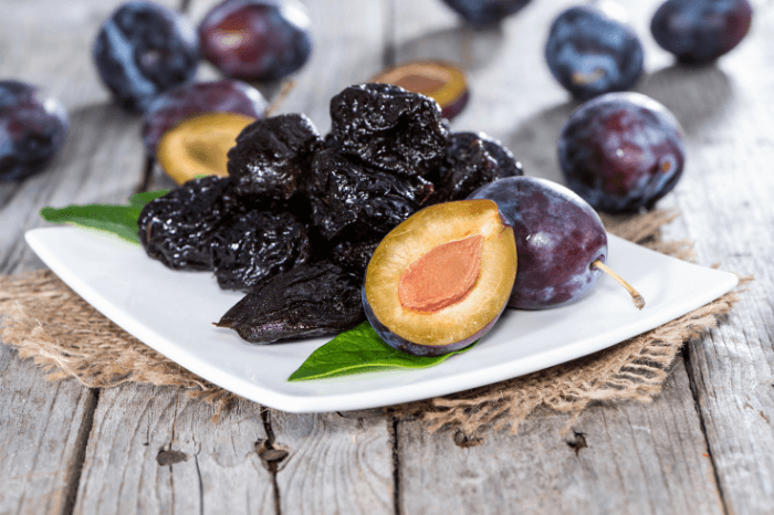 dark purple plums and prunes on a while plate on wood table