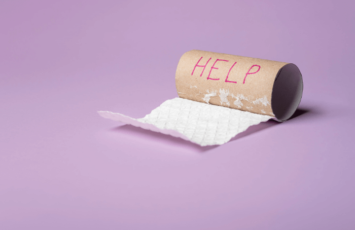 empty toilet paper roll with help written on it in red on purple background