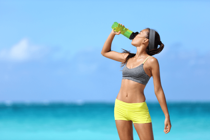 woman at the beach in yellow and gray workout clothes drinking water from green water bottle