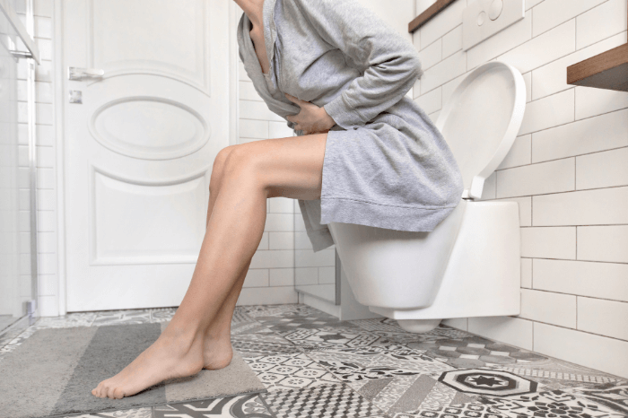 woman sitting on toilet clutching stomach in white and gray bathroom