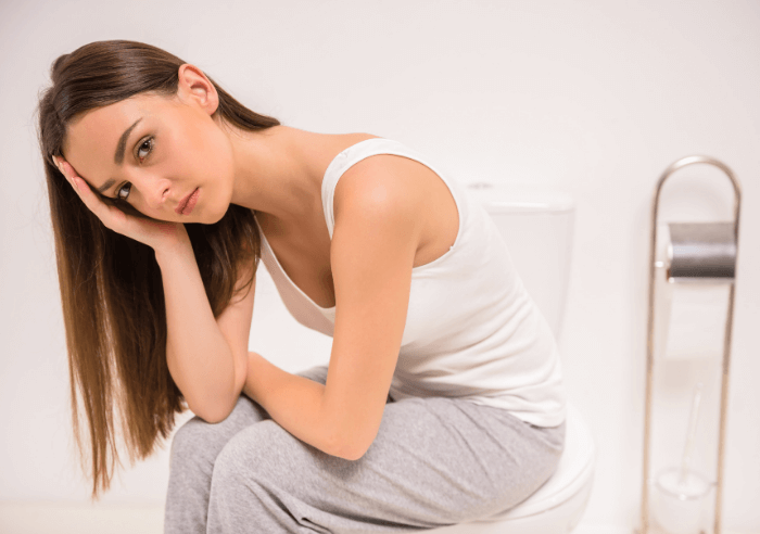 woman sitting on toilet leaning over and holding head with white background