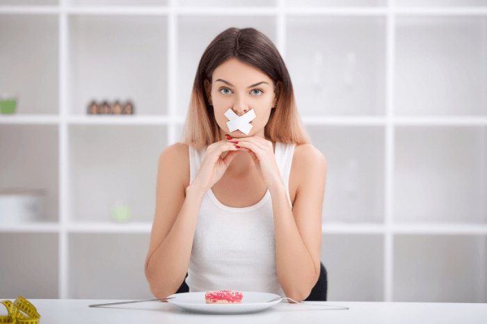 woman with white tape over mouth and donut on plate in front of her with light background