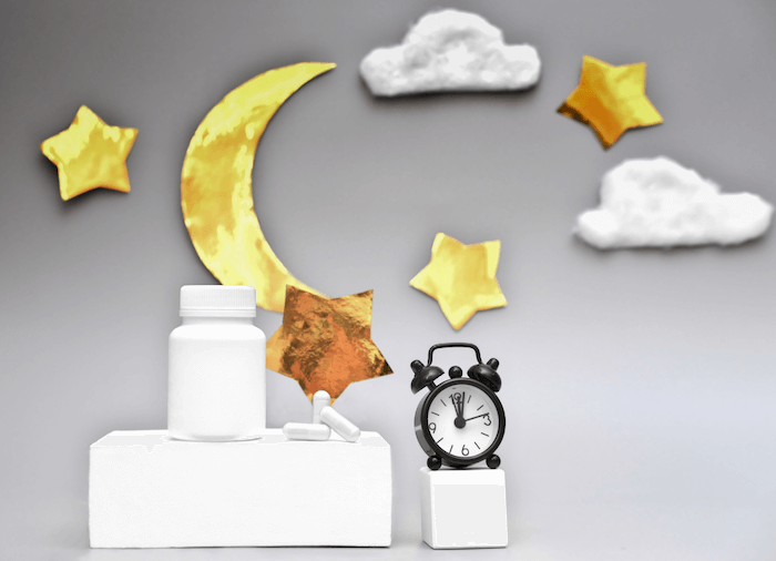 black alarm clock and sleep supplements with cartoon moon stars and clouds on gray background