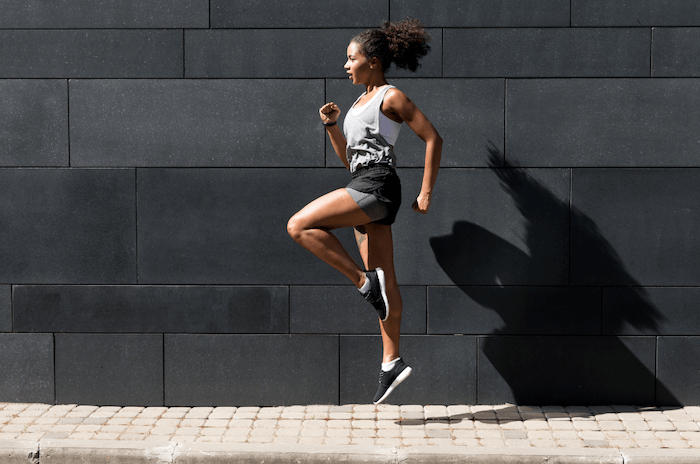 woman in workout clothes and sneakers jumping running outside on sidewalk with black wall