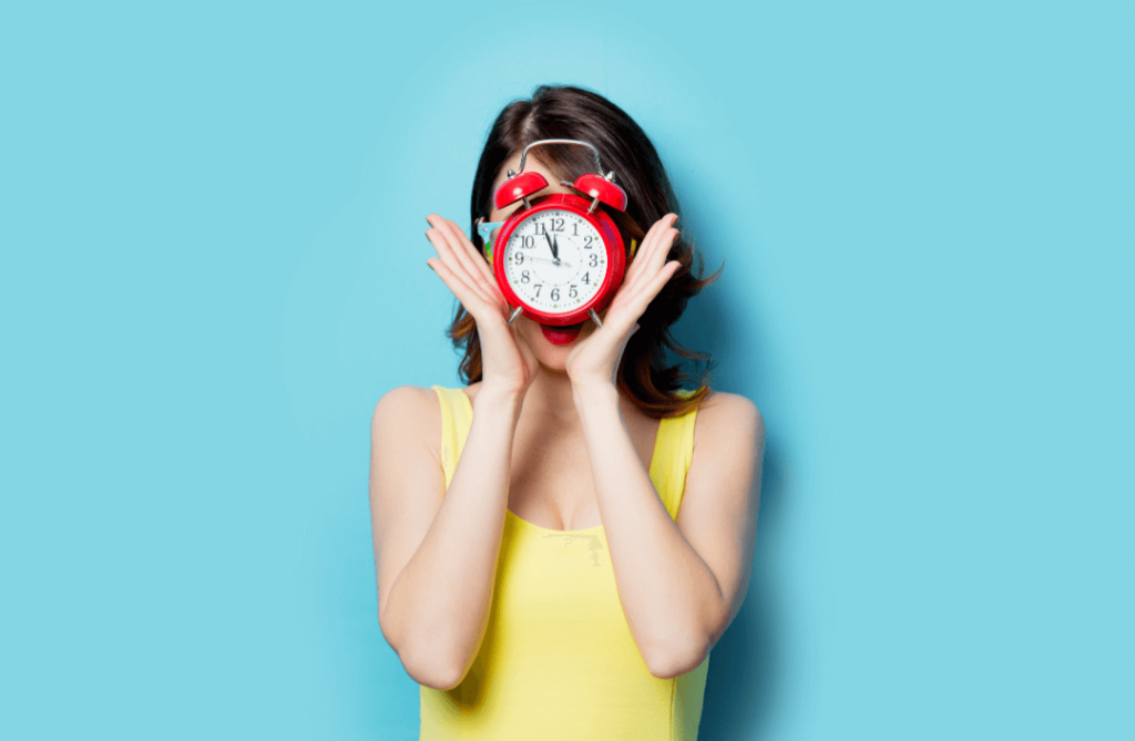woman in yellow shirt holding red alarm clock over her face against a blue background