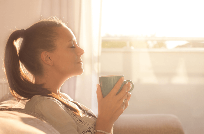 woman sitting enjoying cup of coffee with the sun coming through the window