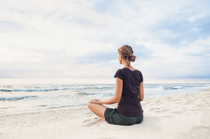 woman sitting on beach facing ocean and practicing relaxation techniques