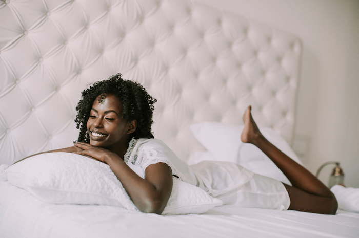 woman wearing white pajamas laying in white bed smiling